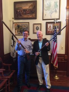 John Cornyn and Dan Patrick standing in Patrick's office holding old-fashioned muskets