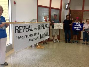 Protestors holding a banner that says Repeal and Replace Representative Michael McCaul