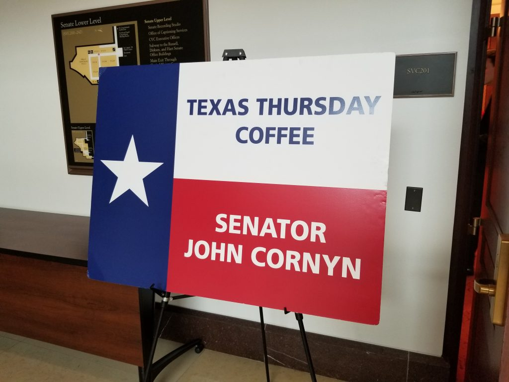 Texas flag sign that say says Texas Thursday Coffee Senator John Cornyn